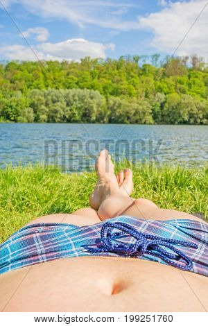 Man With Checkered Bathing Slip And Bare Feet At Lake / River, Meadow / Grass