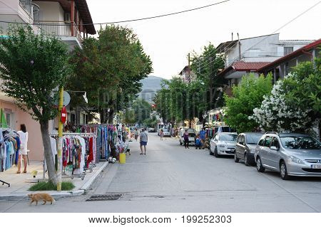 Asprovalta Greece - June 16 2017: summer resort in northern Greece on the Aegean Sea. Street in the evening. Visible numerous shops taverns and strolling tourists. Shops mainly offer souvenirs clothing and beach equipment.