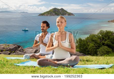 fitness, sport, meditation and people concept - happy couple doing yoga and meditating outdoors over natural background and sea