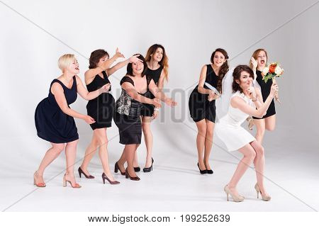Stylish bridesmaids having fun with bride. Cheerful happy girls celebrate a bachelorette party of bride. Bride throwing bouquet for girls to catch. Studio shoot
