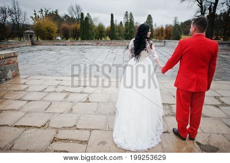 Beautiful Wedding Couple Walking On The Pavement On A Rainy And Cloudy Day.