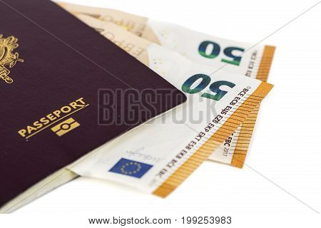 100 euro bills banknotes inserted between pages of european French passport. Concept price travel backchich. Front and top view close-up