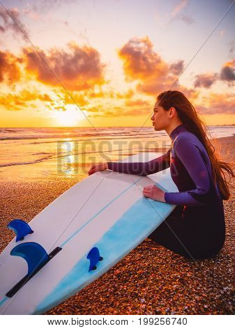 Surfer girl with surfboard relaxed on a beach at warm sunset or sunrise. Surfer and ocean