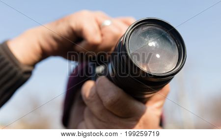 A large lens in the camera of a man .