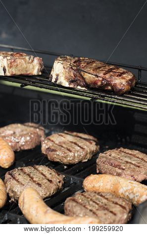 Hamburgers and Sausage being grilled outdoors on a barbecue