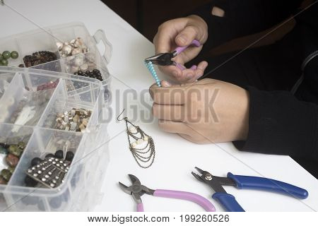 Person making jewelry using wire chains and beads and other materials with craft tools