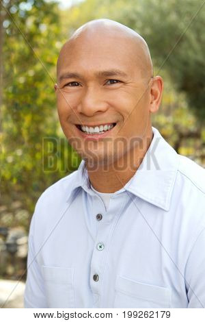 Portrait of a happy Asian Man Smiling Outside.