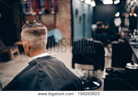 Close-up portrait of a hipster man in a barber shop with a hairdresser. Copyspace. background