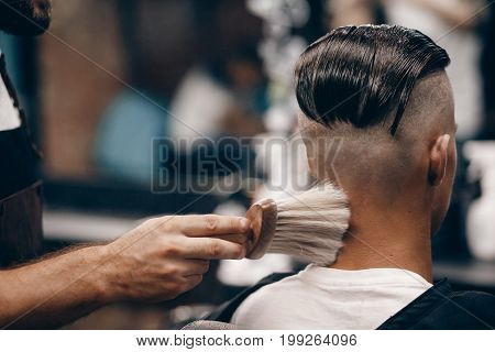 Close-up of a young hipster guy in a barber shop hairdresser shakes his hair, does talc. Concept men's place, toned photo. Soft focus.