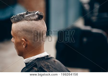 Close-up portrait of a hipster man in a barber shop with a hairdresser. Copy space
