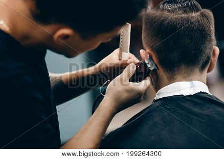 Close-up of a young hipster guy in a barber shop hairdresser cutting hair with scissors and a typewriter, waxing hair, blow-drying. Concept men's place, toned photo. Soft focus.