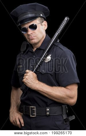 Tough looking uniformed Caucasian police officer wearing sunglasses at night while holding baton over shoulder on black background