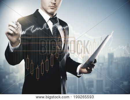 Young businessman with document in hand drawing abstract forex chart on creative city background. Finance success trading and income concept. Double exposure
