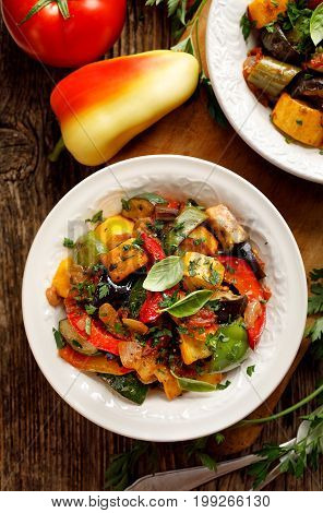 Ratatouille, Vegetarian stew made of zucchini, eggplants, peppers, onions, garlic and tomatoes with aromatic herbs, top view. Traditional french food