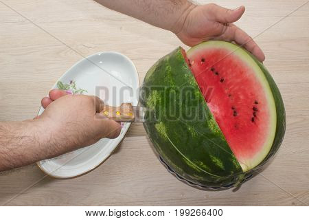 single watermelon cut on wood table at natural background. summer food concept