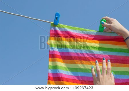 A woman hung washed laundry outdoors. Girl drying laundry on a clothes line in the sun in the outdoor. colored clothespin on the rope outdoor