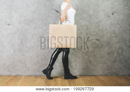 Woman holding empty shopping bag on concrete wall background. Merchandise concept. Mock up