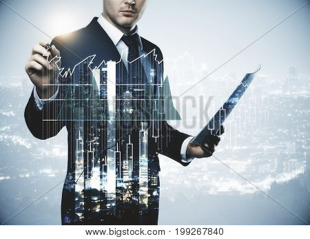 Young businessman with document in hand drawing abstract forex chart on creative city background. Finance success trading and analysis concept. Double exposure