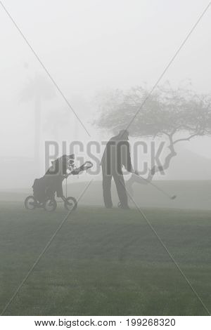 lone golfer completing his round in dense fog.