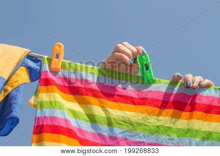 woman hanging clothes on the line outdoors. A woman hung washed laundry outdoors. Girl drying laundry on a clothes line in the sun in the outdoor