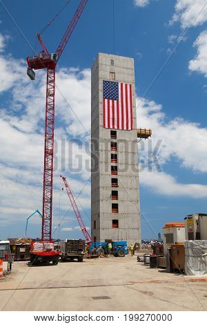Boston Massachusetts USA - July 15 2016 : New construction luxury condos on Fan Pier in Boston. Huge American flag adorns buildings under construction along Harborwalk in South Boston