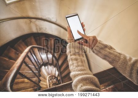 Girl using cellphone on the stairs in the building.