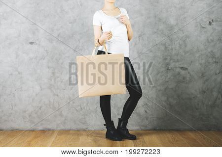 Female holding empty shopping bag on concrete wall background. Consumerism concept. Mock up