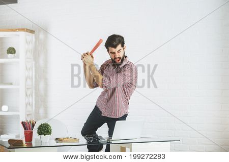 Angry young businessman at workplace about to break his laptop. Stress concept