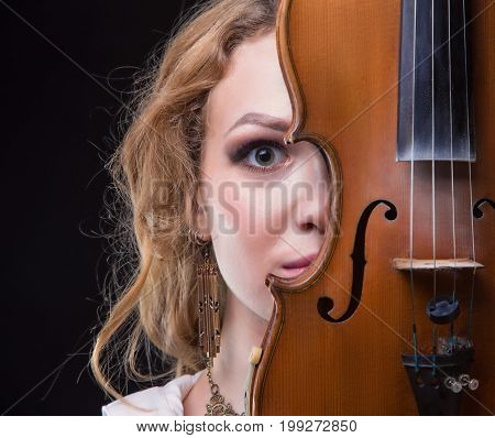 Blond young woman hiding behind violin on black background