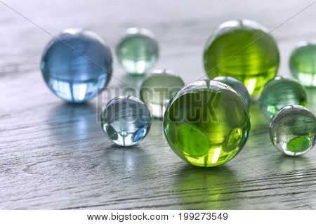 Glass balls of green and blue on a wooden surface