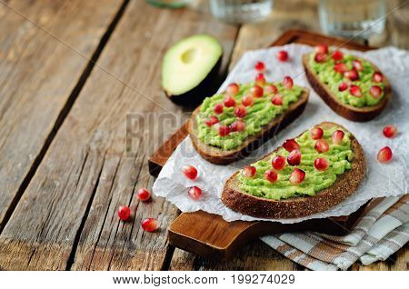 Smashed avocado pomegranate rye sandwiches on a wood background