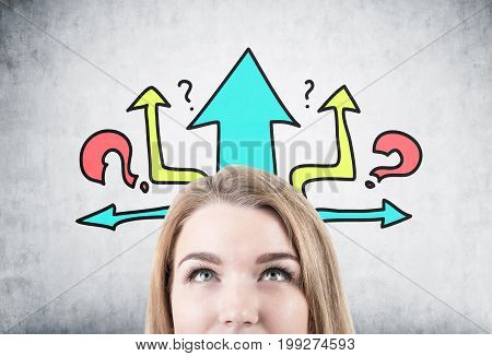 Close up of a head of a beautiful blonde woman looking upwards while standing near a concrete wall with colorful arrows and question marks on it.