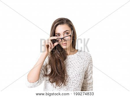 Isolated portrait of a young woman with dark long hair wearing a white sweater and holding her glasses with a thick frame. She is looking to the distance.