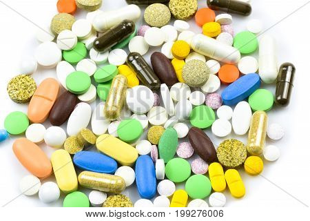 Pile of Pills and Capsules isolated on white and brown background