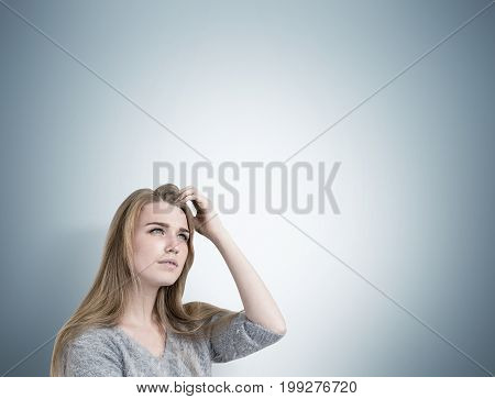 Close up of a blonde businesswoman scratching her head and thinking. She is wearing a gray sweater and trying to recall an idea. Gray wall background mock up