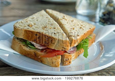 A bacon sandwich on wholegrain granary bread with lettuce and tomato.