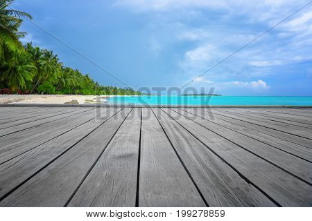 View of tropical beach from wooden pontoon on summer day