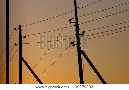 Electric wires on yellow sunset as background .