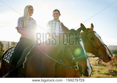 Smiling Couple Talking Together While Riding Horseback In The Afternoon