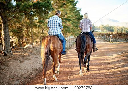 Couple Horseback Riding Together Along A Trail In The Countryside