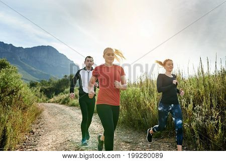 Friends Cross Country Running Together On A Trail