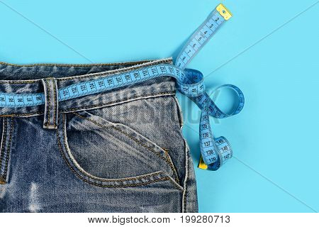 Healthy lifestyle and dieting concept. Close up of jeans with measure tape around waist. Upper part of denim trousers isolated on blue background. Blue jeans with blue measure tape instead of belt.