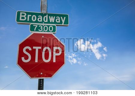 Stop sign against a blue sky on broadway