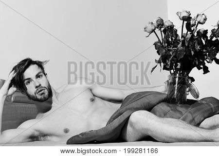young handsome bearded sexy macho man with stylish beard lying naked on bed under red blanket holding transparent vase with bouquet of orange roses and shows abs with muscle torso on athletic body poster