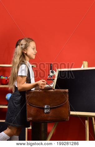 Back To School And Childhood Concept. Girl Stands Near Blackboard