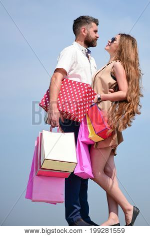 Sexy girl and guy with smiling faces make purchases. Shopping and shopaholism concept. Man with beard and long haired woman hold shopping bags. Couple in love holds pink packets on blue sky background