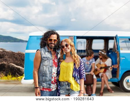 summer holidays, road trip, travel and people concept - smiling young hippie couple with friends in minivan car over island background