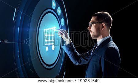 business, people, augmented reality and e-commerce concept - businessman with shopping cart on virtual screen over black background
