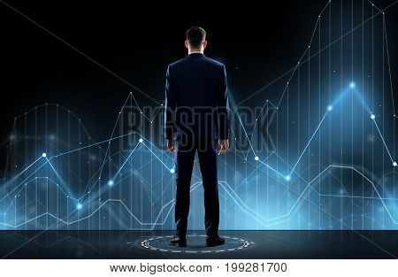 business, technology and people concept - businessman in suit looking at virtual chart over black background from back