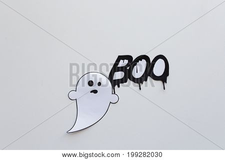 halloween, decoration and scary concept - paper ghost doodle and word boo over white background